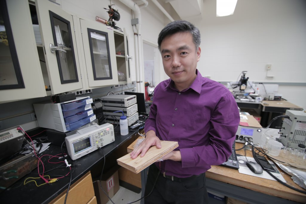 Photo: Associate Professor Xudong Wang holds a prototype of the researchers' energy harvesting technology, which uses wood pulp and harnesses nanofibers. The technology could be incorporated into flooring and convert footsteps on the flooring into usable electricity.